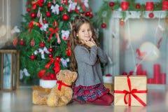 Niña del niño con la caja de regalo cerca del árbol de navidad y de la chimenea en casa Fotos de archivo