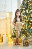 Niña del niño con la caja de regalo cerca del árbol de navidad y de la chimenea en casa Imágenes de archivo libres de regalías