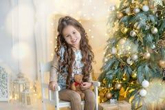 Niña del niño con la caja de regalo cerca del árbol de navidad y de la chimenea en casa Imagen de archivo libre de regalías