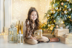 Niña del niño con la caja de regalo cerca del árbol de navidad y de la chimenea en casa Fotos de archivo libres de regalías