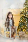 Niña del niño con la caja de regalo cerca del árbol de navidad y de la chimenea en casa Foto de archivo