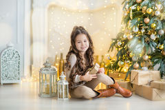 Niña del niño con la caja de regalo cerca del árbol de navidad y de la chimenea en casa Imagenes de archivo