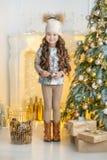 Niña del niño con la caja de regalo cerca del árbol de navidad y de la chimenea en casa Foto de archivo libre de regalías