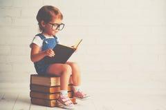 Niña del niño con la lectura de los vidrios libros Fotografía de archivo libre de regalías