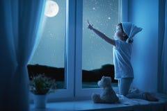 Niña del niño en la ventana que sueña y que admira el cielo estrellado en