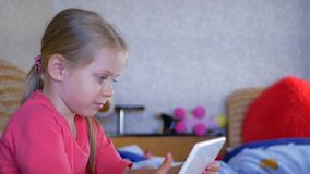 Niña del niño hermoso que juega con una tableta almacen de video