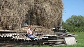 Niña del país que juega la tableta al aire libre en la muchacha del pueblo que se relaja en la naturaleza 4K