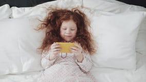 Niña del pelirrojo que cae en su cama con el teléfono móvil amarillo Ella que ríe y que se divierte, usando la cámara lenta  metrajes