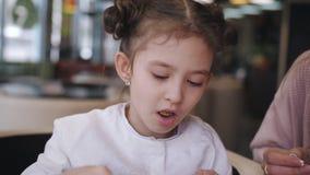 Niña del primer en un café que come la pizza con la mamá almacen de video