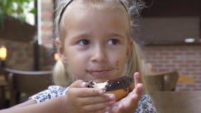 Niña del retrato que come el buñuelo del chocolate dulce en la tabla en café Buñuelo del chocolate de la muchacha rubia linda de  almacen de video