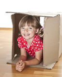 Niña dentro de una caja de cartón Imágenes de archivo libres de regalías