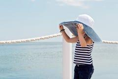 Niña divertida (3 años) en sombrero grande en la playa Foto de archivo libre de regalías