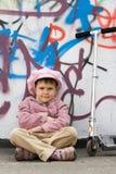 Niña divertida con la vespa cerca de la pared de la pintada Imagen de archivo