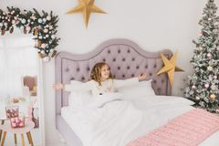 Niña divertida el mañana de la Navidad en el interior casero blanco Fotos de archivo libres de regalías