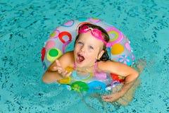 Niña divertida en gafas rosadas en la piscina imagenes de archivo