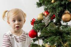 Niña divertida feliz de la Navidad que viste para arriba un árbol de navidad en un fondo blanco Foto de archivo libre de regalías