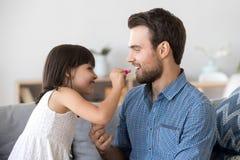 Ni?a divertida hacer los labios de la pintura del maquillaje para el pap? joven fotografía de archivo