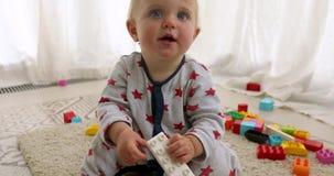 Niña divertida linda en una camisa colorida que juega con los bloques del juguete de la construcción metrajes
