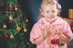 Niña divertida que adorna el árbol de navidad Fotografía de archivo libre de regalías