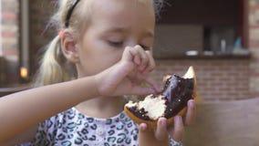 Niña divertida que come el buñuelo del chocolate dulce en la tabla en café Buñuelo del chocolate de la muchacha rubia linda de la almacen de metraje de vídeo