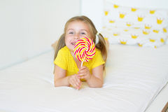 Niña divertida que come la piruleta grande del azúcar Imagen de archivo libre de regalías