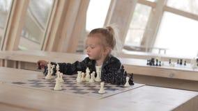 Niña divertida que juega a ajedrez con los pedazos de ajedrez en un club almacen de metraje de vídeo