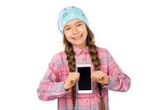 Niña divertida que muestra el teléfono elegante con la pantalla en blanco en el fondo blanco Jugar juegos y el vídeo del reloj fotos de archivo