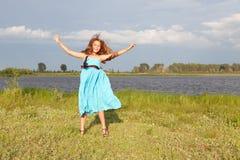 Niña divertida que salta en el campo verde, verano Imagen de archivo