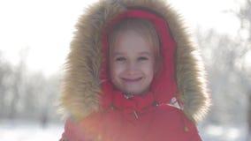 Niña divertida que se divierte en parque hermoso del invierno El retrato del invierno de la pequeña muchacha adorable mira en la  almacen de metraje de vídeo
