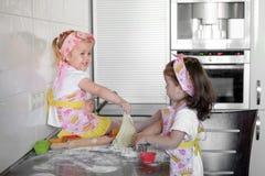 Niña dos que prepara las galletas en cocina en casa foto de archivo libre de regalías