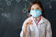 Niña dotada que disfruta de tareas médicas en la escuela Imagen de archivo