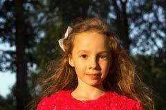 Niña dulce al aire libre con el pelo rizado en el viento Foto de archivo libre de regalías