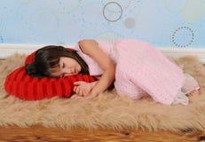 Niña dulce dormida en la almohadilla en forma de corazón Fotos de archivo