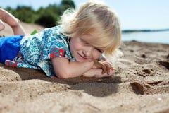 Niña dulce que miente en la playa en parque Fotos de archivo libres de regalías