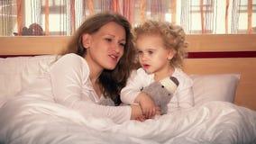 Niña dulce y su nana joven hermosa del canto de la mamá para el oso del juguete almacen de video