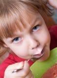 Niña durante una comida Imagenes de archivo