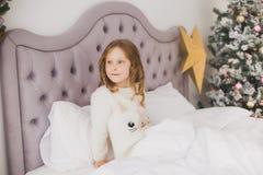 Niña el mañana de la Navidad en el interior casero Imágenes de archivo libres de regalías