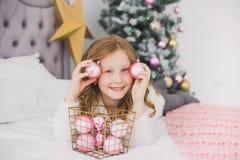 Niña el mañana de la Navidad en el interior casero Foto de archivo