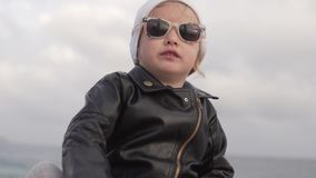 Niña elegante en la charla de cuero de la chaqueta de cuero y de las gafas de sol almacen de video