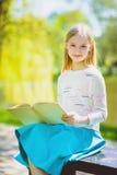 Niña elegante feliz que sonríe sosteniendo el libro al aire libre Foto de archivo