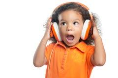 Niña emocionada con un peinado afro que disfruta de su música en los auriculares anaranjados brillantes Imagen de archivo