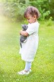 Niña emocional que juega con un gato en el parque Fotos de archivo libres de regalías