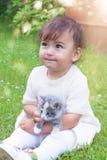 Niña emocional que juega con un gato en el parque Fotografía de archivo