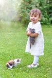 Niña emocional que juega con un gato en el parque Imagen de archivo libre de regalías
