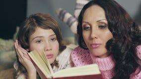 Niña empathizing con los caracteres de los cuentos de hadas, leyendo con la madre metrajes