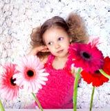 Niña en actitudes rosadas del vestido entre las flores Fotos de archivo