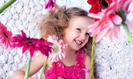 Niña en actitudes rosadas del vestido entre las flores Fotografía de archivo libre de regalías