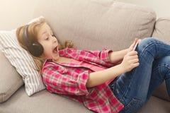 Niña en auriculares con smartphone en casa Imagenes de archivo