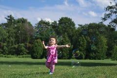 Niña en burbujas de cogida del equipo rosado Fotos de archivo libres de regalías