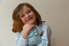 Niña en camisa rayada con el pelo rubio sucio sucio que abraza su oso de peluche foto de archivo